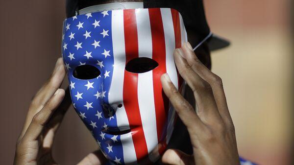 Мужчина в маске с флагом США. Архивное фото