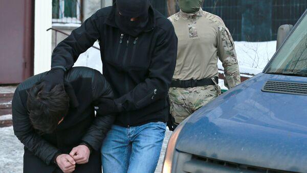 Силовики выводят из подъезда дома № 11 на улице Наметкина участника диверсионно-террористической группы, готовившей серию терактов в Москве