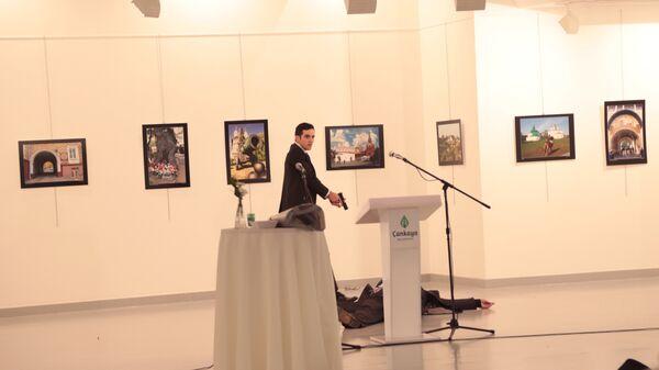 Вооруженный мужчина рядом с телом посла РФ в Турции Андрея Карлова в галерее в Анкаре. Фотография Бурхана Озбилиджи