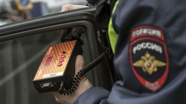 Сотрудник ГИБДД проверяет с помощью прибора тонировку стекла автомобиля в рамках рейда скрытых патрулей ДПС в Москве