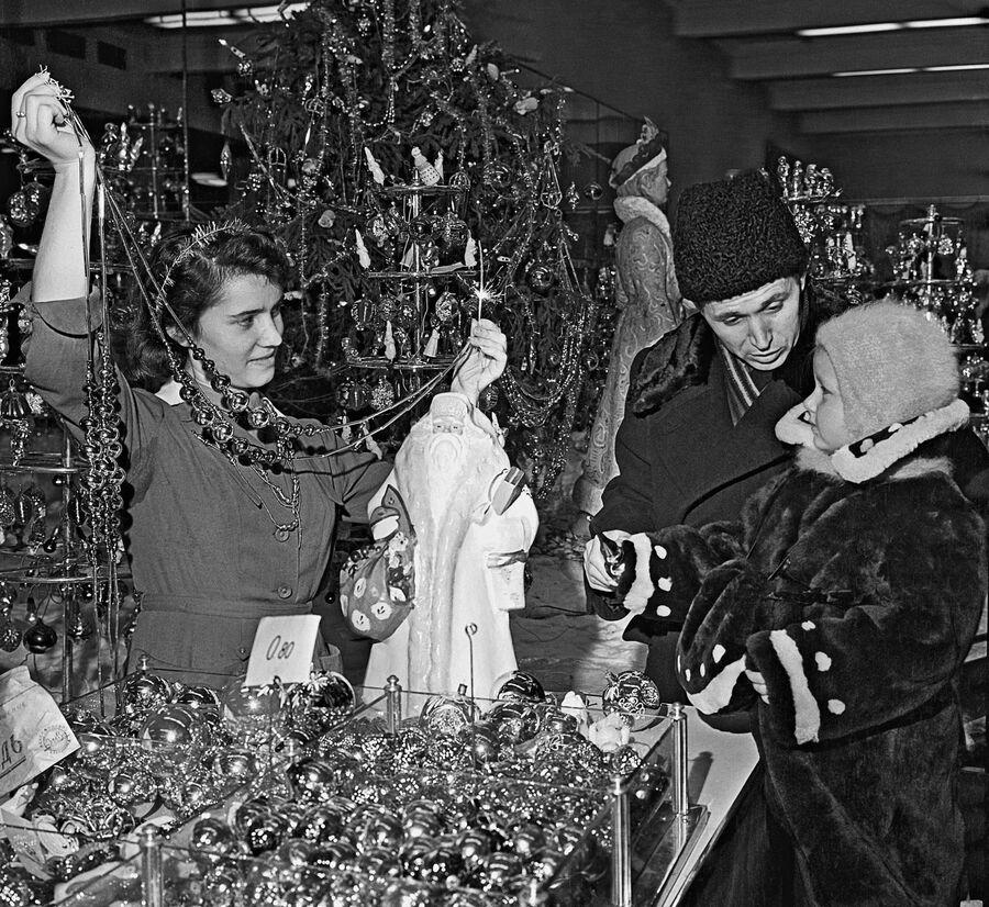 Папа с маленькой дочкой выбирают ёлочные украшения в магазине Детский мир в Москве