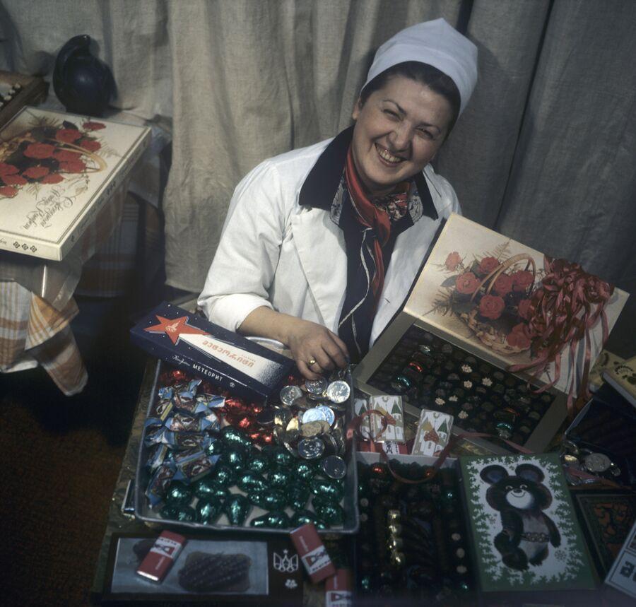 Бригадир бригады коммунистического труда Тбилисской кондитерской фабрики Мавра-Кобахадзе Рухадзе со сладкой продукцией предприятия