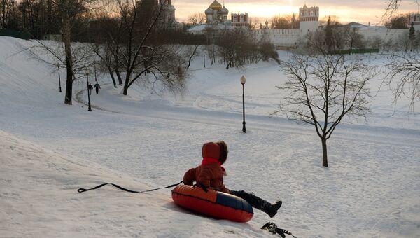 Ребенок катается с горы на берегу Большого Новодевичьего пруда в Москве