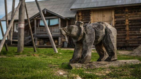 Деревянная фигура медведя на детской площадке в деревне Кинерма в Карелии