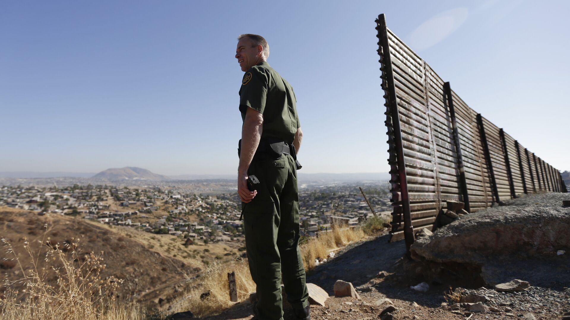 Сотрудник правоохранительных органов США у стены на границе США и Мексики - РИА Новости, 1920, 21.01.2021
