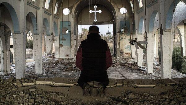 Житель одной из деревень в провинции Эль-Хасаке молится в храме Святого Георгия, разрушенного боевиками ИГ. Сирия, 08.12.2015