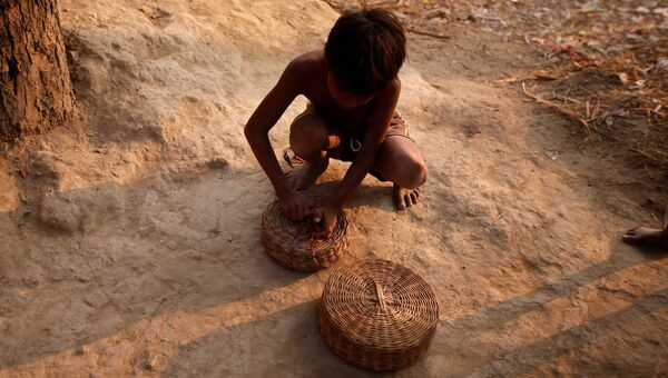 Мальчик закрывает корзину для змей в поселении заклинателей змей Jogi Dera в штате Уттар-Прадеш, Индия