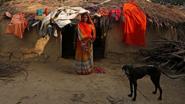Жена заклинателя змей возле своего дома в поселении заклинателей змей Jogi Dera в штате Уттар-Прадеш, Индия