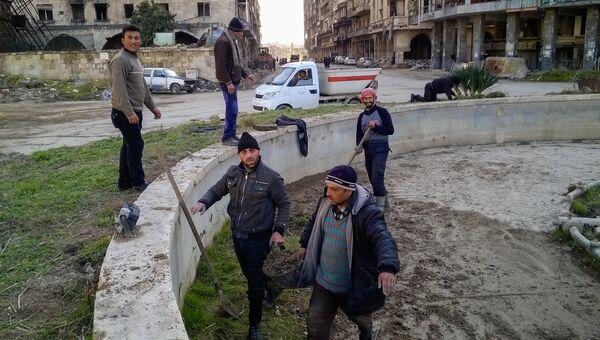 Горожане во время уборки на улице в районе Аль Назирия в сирийском Аллепо. 11 января 2017 год