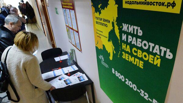 Посетители возле стенда с информационными буклетами в коридоре Департамента имущественных и земельных отношений Приморского края, где проходит вручение сертификатов на дальневосточные гектары