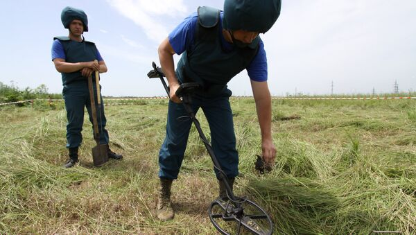 Саперы МЧС ДНР обследуют с миноискателем участок поля в районе города Дебальцево