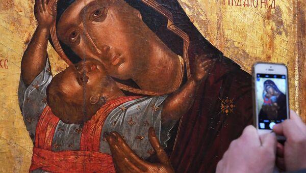 Посетитель фотографирует икону Богоматерь с младенцем. Архивное фото