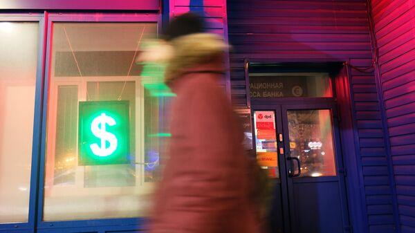Табло со знаком доллара в витрине операционной кассы банка. Архивное фото.