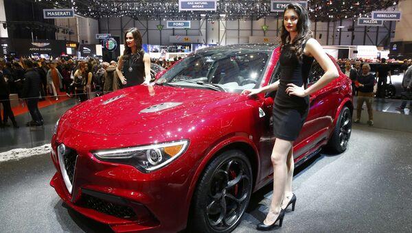 Модели позируют возле автомобиля Alfa Romeo Stelvio на Женевском международном автосалоне