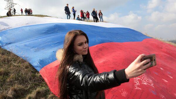 Девушка делает селфи на фоне огромного флага России на фестивале Крымская весна в селе Мирное Симферопольского района Республики Крым