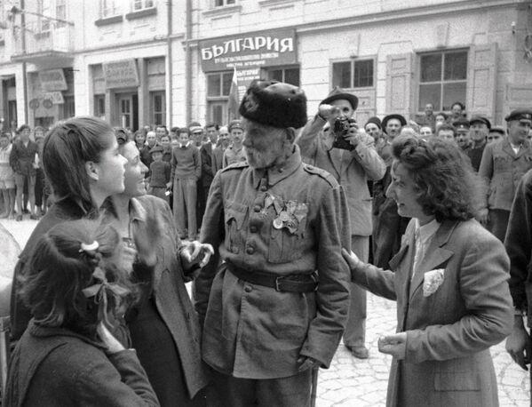 Ветеран турецкой войны беседует с девушками, в освобожденном войсками РККА от фашистов, болгарском городе