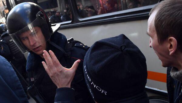 Сотрудник полиции (слева) и участники несанкционированной акции на Триумфальной площади в Москве.