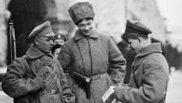 Вооруженные красногвардейцы читают листовку на улице Петрограда