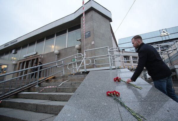 Мужчина возлагает цветы у входа в вестибюль станции метро Сенная площадь в Санкт-Петербурге