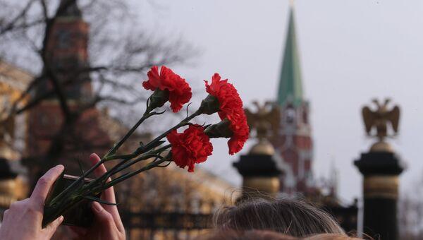 Цветы в руках участника акции памяти и солидарности Питер - Мы с тобой! в Москве