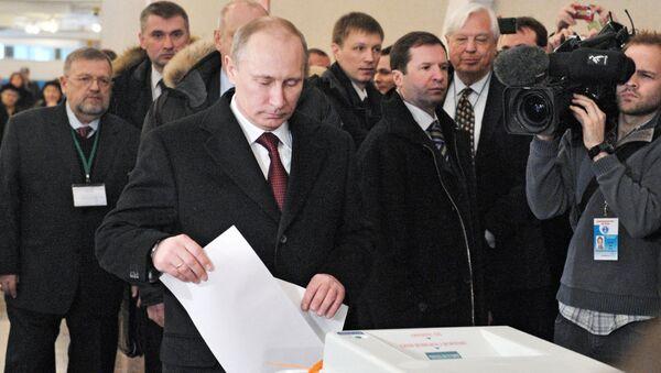 Кандидат в президенты РФ, председатель правительства России Владимир Путин опускает бюллетень в урну для голосования на избирательном участке № 2079 на выборах президента РФ в Российской академии наук. 4 марта 2012 года