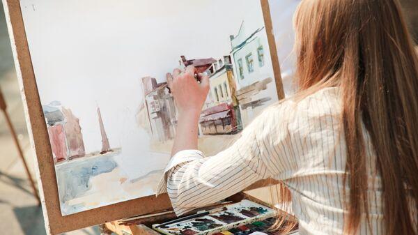 Девушка рисует левой рукой