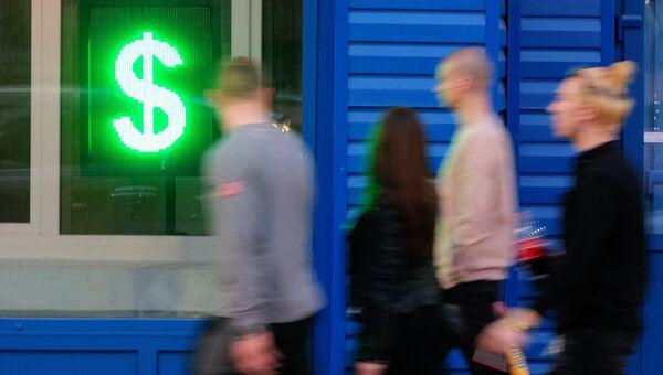 Знак доллара на табло курса обмена валют в витрине операционной кассы в Москве