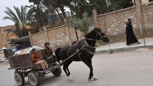 Люди на телеге на улице в сирийском городе Дейр-эз-Зор. Архивное фото