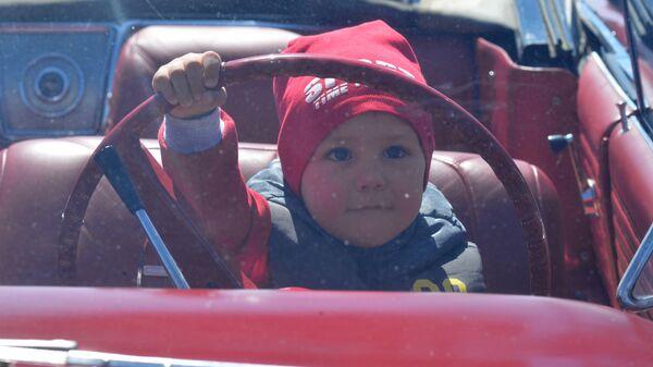 Ребенок за рулем автомобиля на международном фестивале ретро-автомобилей