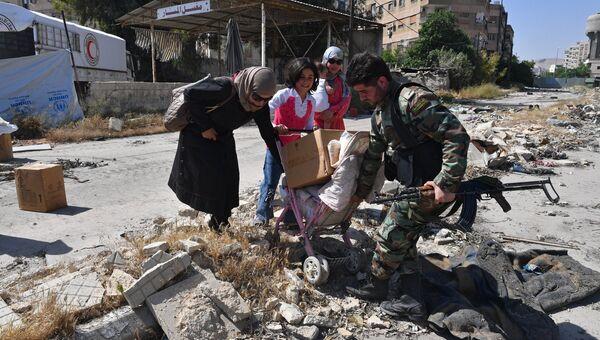 Жители квартала Кабун в пригороде Дамаска во время раздачи гуманитарной помощи. Архивное фото