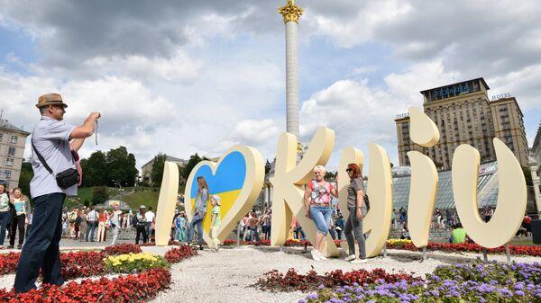 Люди фотографируются у инсталляции в Киеве во время празднования Дня города