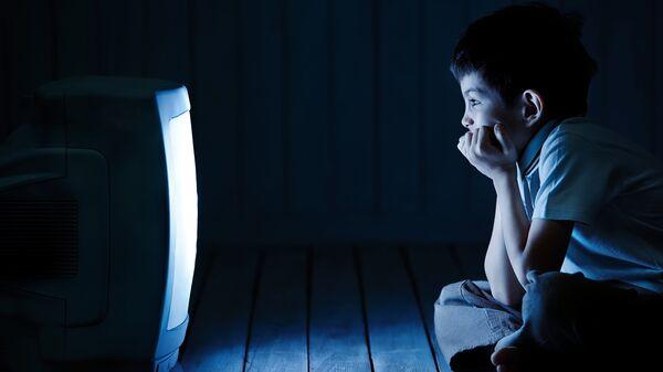 Мальчик смотрит телевизор ночью