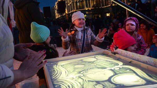 Дети на мастер-классе рисунка песком на стекле на фестивале Красная площадь в Москве