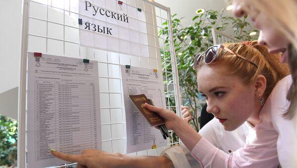 Ученики смотрят списки допущенных к сдаче единого государственного экзамена по русскому языку. 9 июня 2017