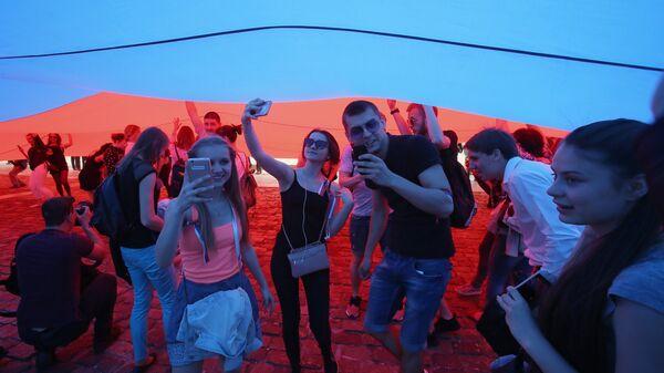 Горожане на Поклонной горе в Москве, где курсанты МЧС России развернули флаг РФ в честь Дня России. 12 июня 2017