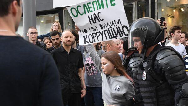 Полицейские задерживают участницу несанкционированной акции на Тверской улице в Москве. 12 июня 2017