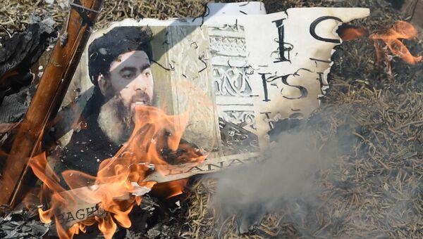 Горящая фотография лидера Исламского государства (ИГ, запрещена в РФ) Абу Бакра аль-Багдади. Архивное фото
