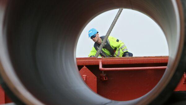 Рабочие подготовливают трубы для строящегося газопровода Северный поток к погрузке на судно доставки