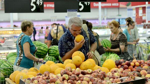 Покупатели в отделе фруктов гипермаркета