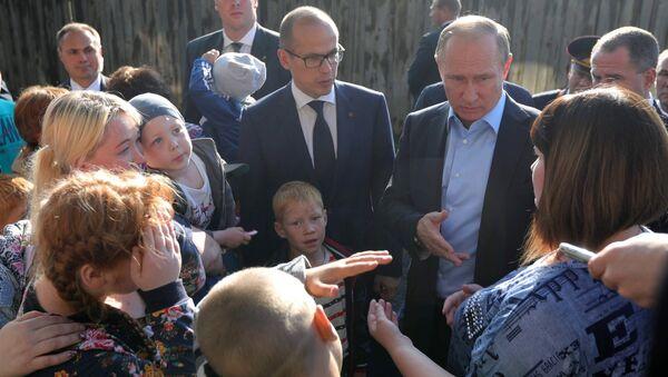 Владимир Путин общается с жителями во время посещения аварийного жилья семьи Анастасии Вотинцевой в Ижевске. 27 июня 2017