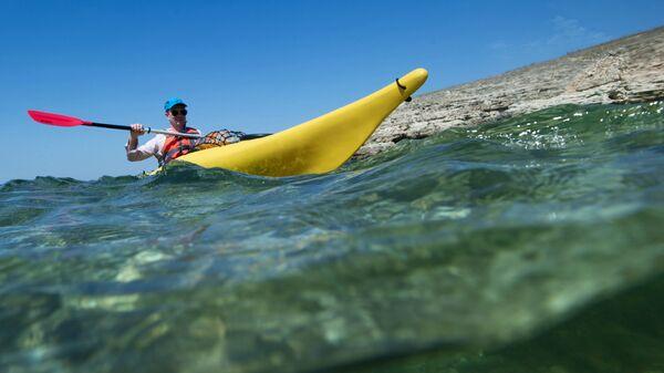 Турист плывет на каяке вдоль берега Черного моря на мысе Тарханкут в Крыму