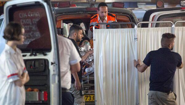 Медики эвакуируют израильтянку, которая была ранена во время нападения с ножом в еврейском поселении Неве Цуф на Западном берегу реки Иордан. 21 июля 2017