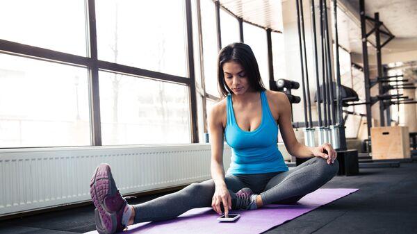 Девушка использует смартфон во время тренировки