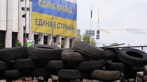 Оставшиеся после акций сторонников Евроинтеграции баррикады из автомобильных покрышек и национальный флаг Украины с надписью Единая страна на русском и украинских языках
