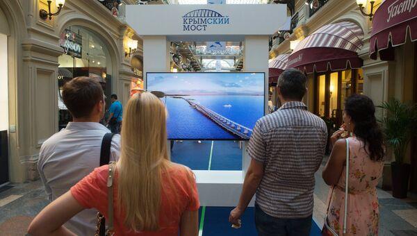 Посетители на выставке, посвященной Крымскому мосту, открывшейся в московском ГУМе на Красной площади. 27 июля 2017
