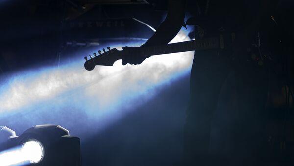 Музыкант с гитарой на сцене