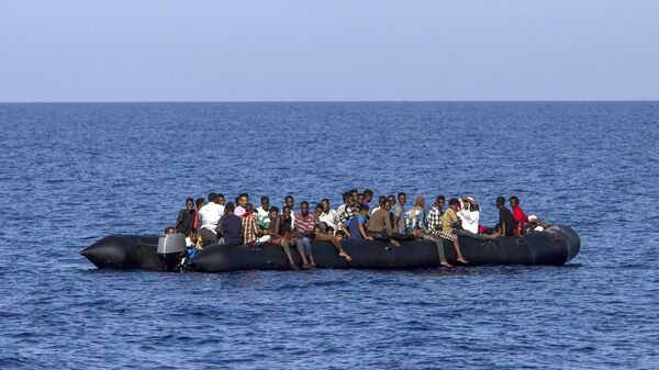 Мигранты около ливийского побережья ждут спасения итальянской береговой охраны. 6 августа 2017