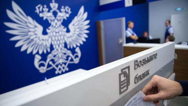 Посетитель берет бланк в отделении Почты России. Архивное фото