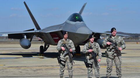 Американские военнослужащие возле истребителя F-22 на базе ВВС США Осан в Пхентхэке, Южная Корея