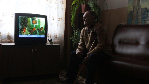 Пенсионер смотрит телевизор в Старорусском доме-интернате для престарелых и инвалидов Приильменье